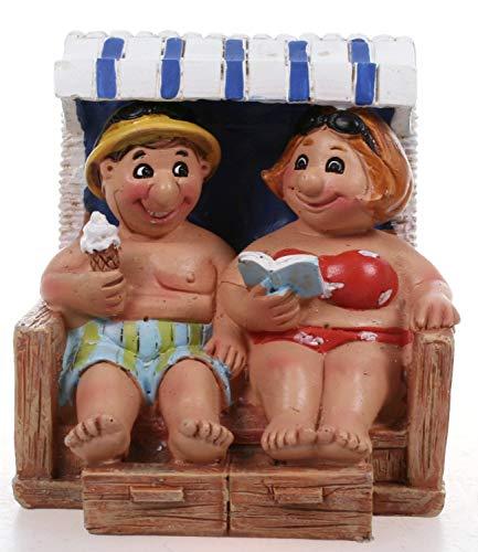 Fröhliches Urlauberpaar im Strandkorb mit Eis und...